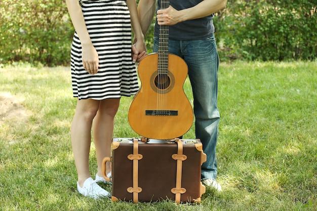 Молодая пара со старинным чемоданом и гитарой на открытом воздухе