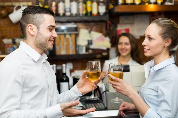 Молодая пара с вином в баре