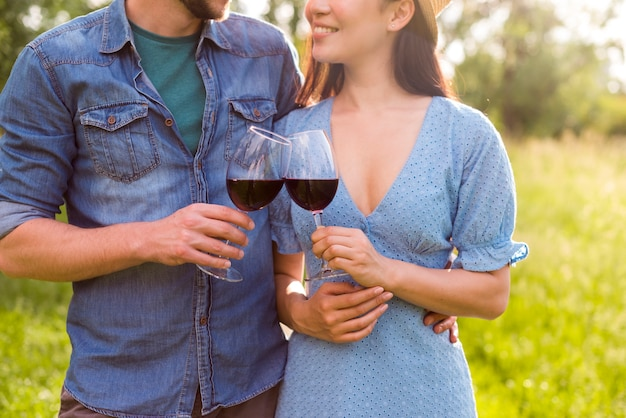 Young couple with wine glasses in park