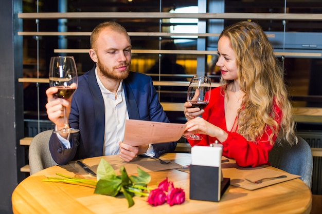 Young couple with wine glasses reading menu