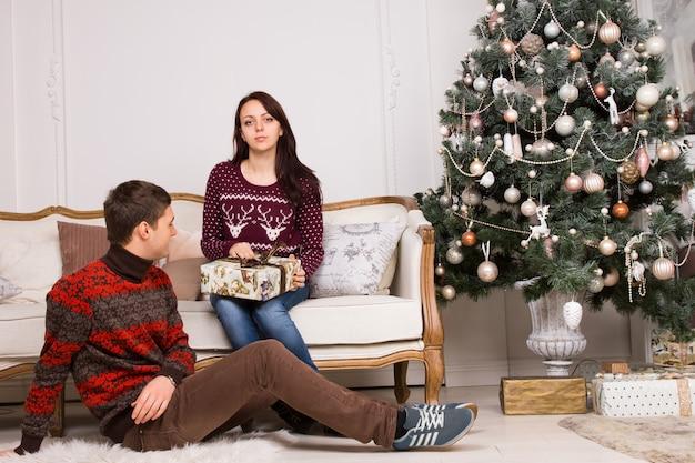 プレゼントとエレガントなソファに座って、カメラを見て、床で休んでいるパートナーと女性と若いカップル。さまざまな装飾が施されたクリスマスツリーの装飾の近くで撮影されました。