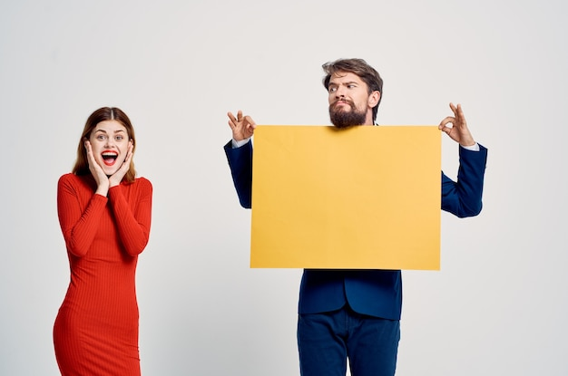 Young couple with yellow mockup advertising emotions sale copy space