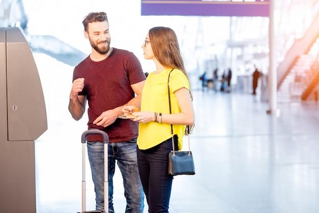 여행하는 동안 공항에서 atm을 사용하여 돈을 인출하는 젊은 부부