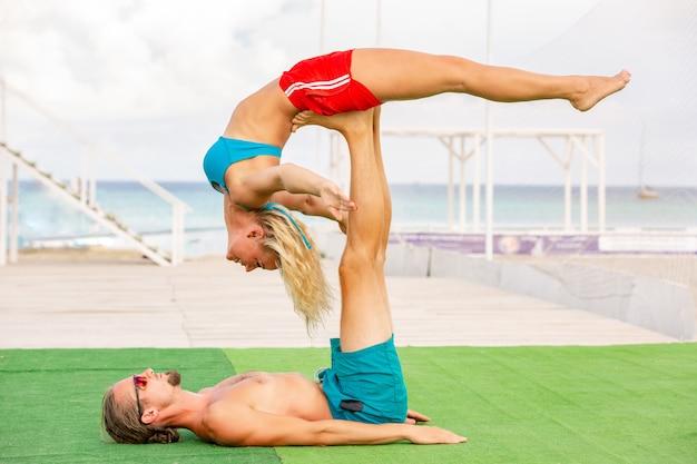 若いカップルの女性と男性のフィットネスヨガを一緒にやっているフィールドに。強さとバランスのアクロヨガ要素