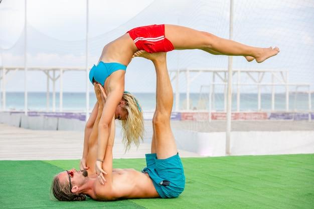 若いカップルの女性と男性のフィットネスヨガを一緒にやっているフィールドに。