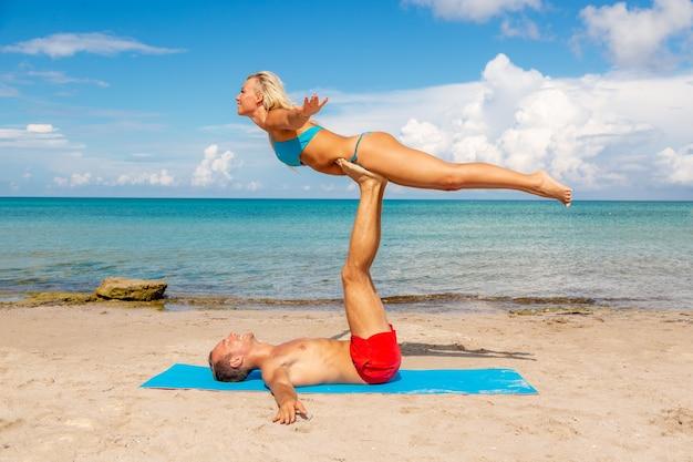 一緒にフィットネスヨガの練習をしているビーチで若いカップルの女性と男性。強度とバランスのためのアクロヨガ要素