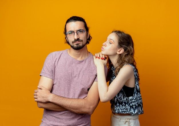 オレンジ色の壁を越えて腕を組んで立って戦った後、許しを求める若いカップルの女性は男を不快にさせた
