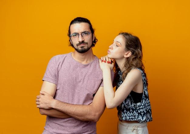 Giovane donna coppia che chiede perdono uomo scontento dopo la lotta in piedi con le braccia incrociate sul muro arancione