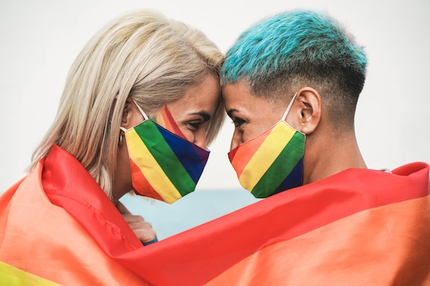 Young couple of women hugging under rainbow flag wearing colorful masks at gay pride event