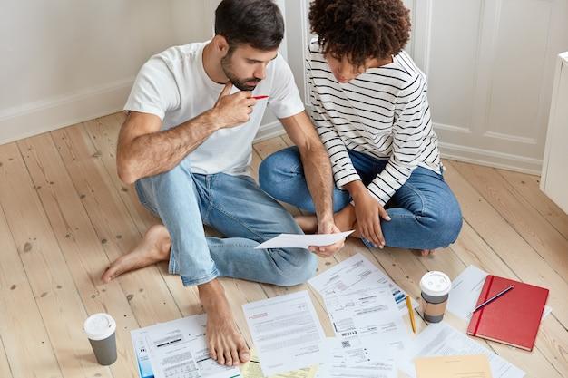 床で一緒に自宅で働く若いカップル
