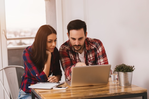Young couple working together on laptop at home