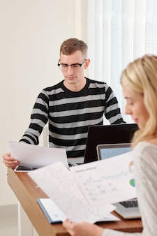 Young couple working with financial documents at table when staying home due to coronavirus pandemic