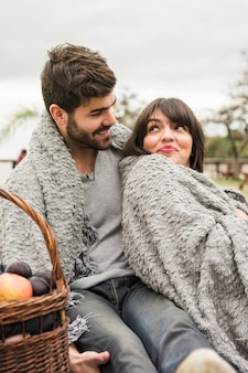 Young couple wrapped in gray blanket looking at each other