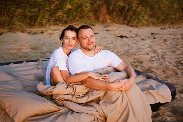 Молодая пара, завернутые в одеяло на открытом воздухе, счастливая влюбленная пара, лежа и вращаясь в постели у моря на закате, счастливая кавказская пара мужа и жены, завернутые в одеяло на открытом воздухе