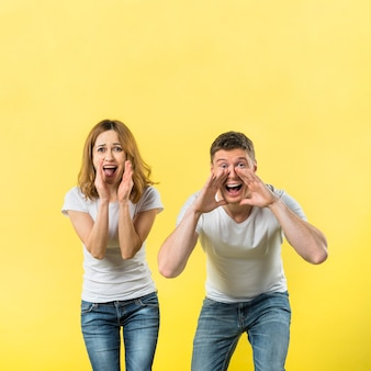 Young couple yelling loudly against yellow background