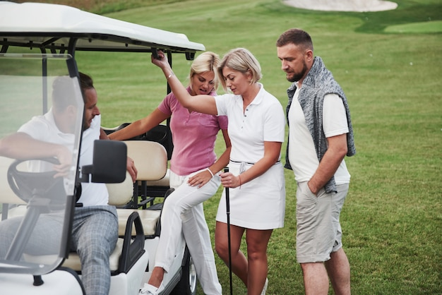 Young couples getting ready to play. a group of smiling friends came to the hole on a golf cart