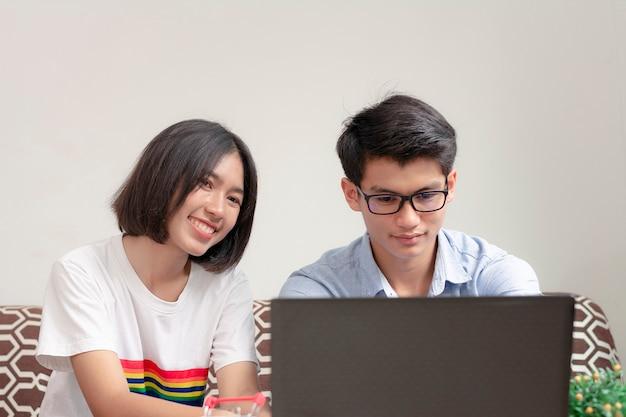 若いカップルはオンラインで勉強して仕事をするためにラップトップをプレイしています。