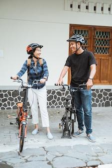 若いカップルは外出前に折りたたみ自転車を準備し、ヘルメットを着用します