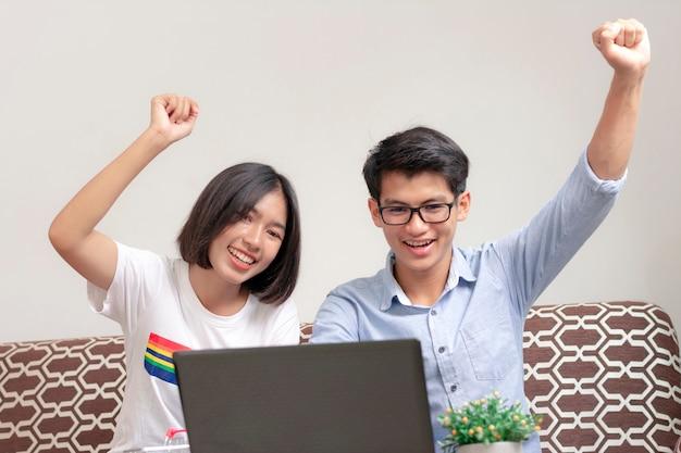 젊은 커플은 손을 보여주고 집에서 노트북을 즐기고 있습니다.