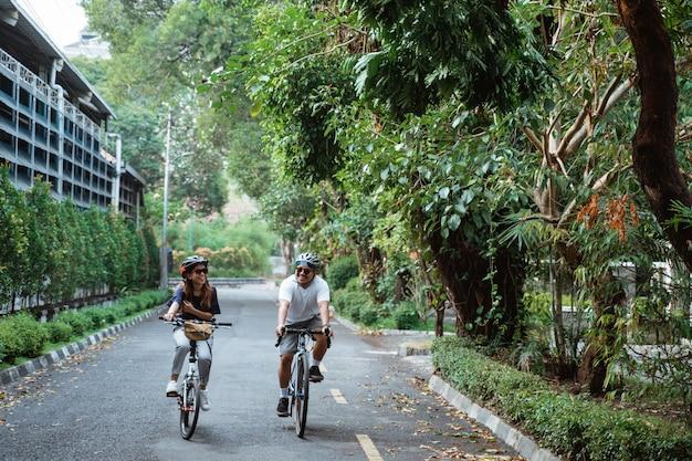 ヘルメットをかぶっている若いカップルが一緒に自転車に乗って楽しむ