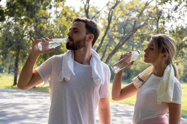 公園で運動した後、水を飲む若いカップル。