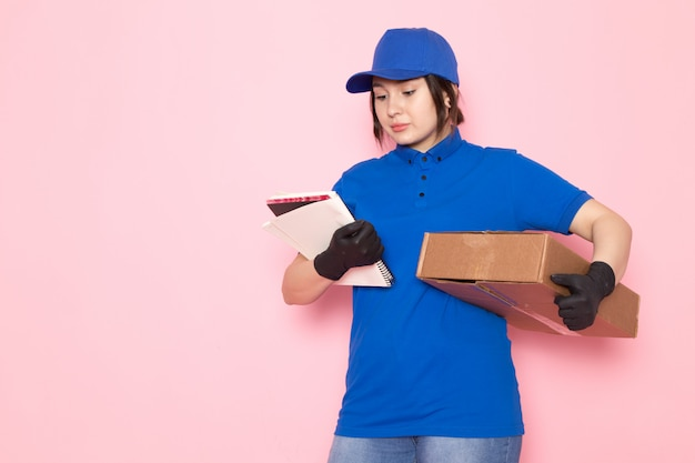 Young courier in blue polo blue cap jeans holding package copybook on pink