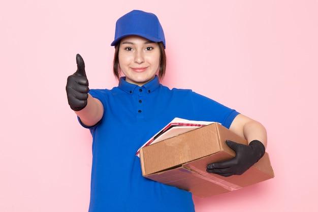Giovane corriere in polo blu jeans blu con cappuccio in possesso di pacchetto sul rosa
