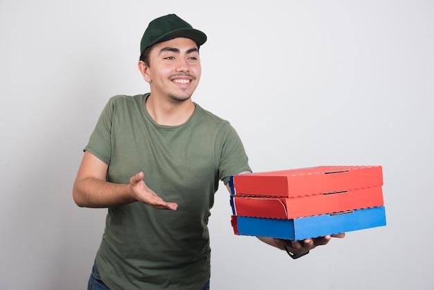 白い背景にピザの3箱を運ぶ若い宅配便。高品質の写真