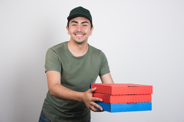Young courier carrying three boxes of pizza on white background.