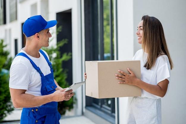 Молодой курьер доставляет товары молодой женщине дома