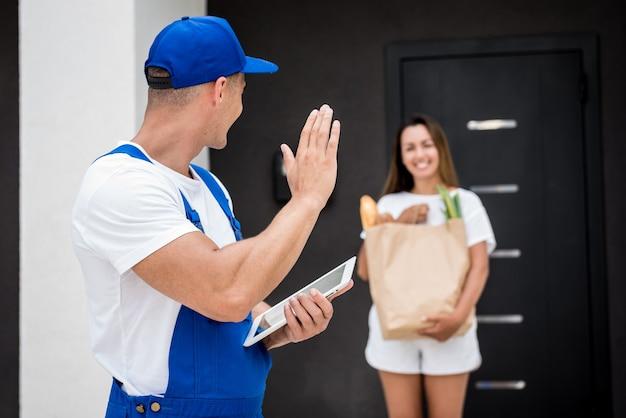 自宅の若い女性に商品を配達する若い宅配便
