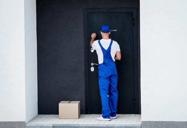 若い宅配便業者が家のドアに商品を配達します。