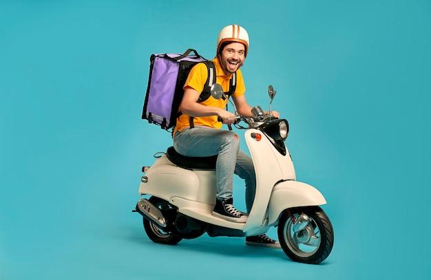 젊은 택배, 절연 오토바이에 열 배낭 제복을 입은 배달 남자. 빠른 운송 특급 택배. 온라인 주문.