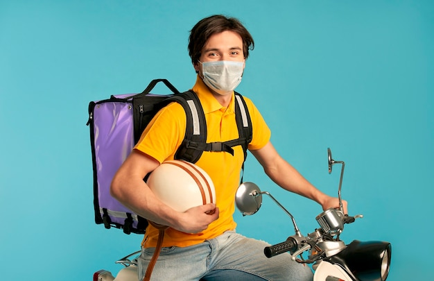 Young courier, delivery man in uniform and protective mask with thermo backpack on a moped isolated. fast transport express home delivery. online ordering during quarantine.