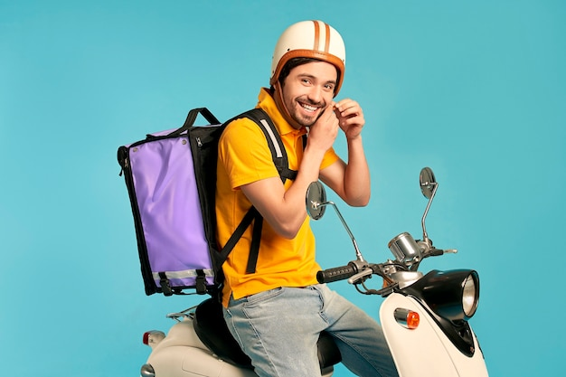 Young courier, delivery man in uniform with thermo backpack on a moped isolated. fast transport express home delivery. online order.