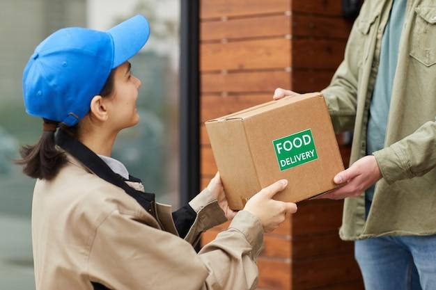 Молодой курьер дает мужчине картонную коробку, пока они стоят на улице, она доставляет еду
