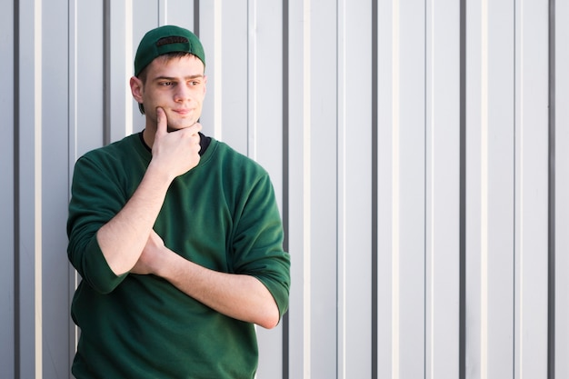 Young courier in green cap touching chin
