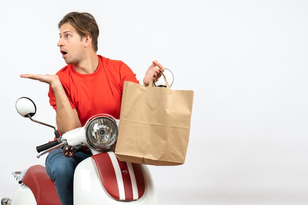 Young courier guy in red uniform sitting on scooter holding paper bag and looking at something on the right side with suprising facial expression on white wall