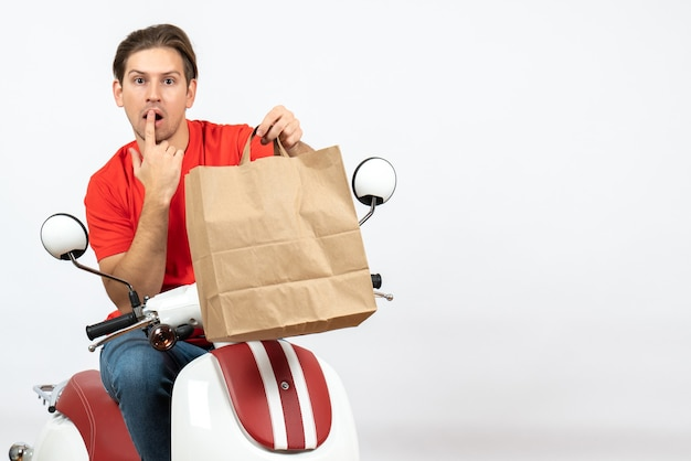 Ragazzo giovane corriere in uniforme rossa che si siede sullo scooter che tiene il sacchetto di carta pensando profondamente sul muro bianco