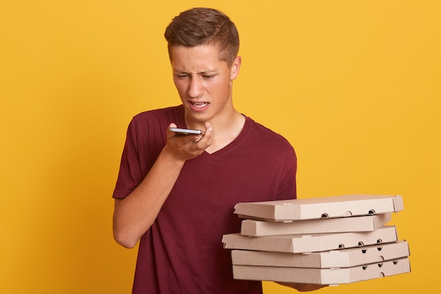 Young courier having unpleasant conversation with client over phone, holding boxes with pizza