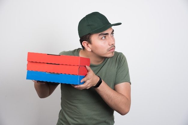 Young courier holding three boxes of pizza on white background.