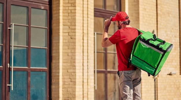 햇살 가득한 고객 집 근처에 보온 가방이 서 있는 빨간 제복을 입은 젊은 택배