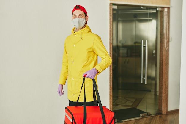 현대 사무실 벽에 서서 점심을 배달하는 동안 고객의 주문으로 큰 빨간 가방을 들고 제복을 입은 젊은 택배