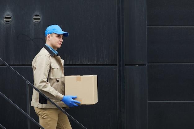 Молодой курьер в униформе спускается по лестнице и несет коробку