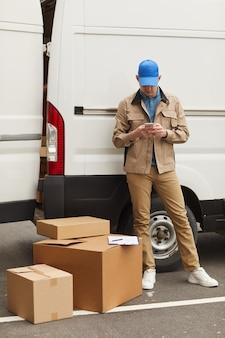 屋外のバンに対してボックスの近くに立っている間彼の携帯電話を使用して制服を着た若い宅配便