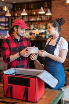 Молодой курьер в спецодежде берет пластиковый контейнер с едой из рук официантки, помогая ему упаковывать заказы клиентов в кафе