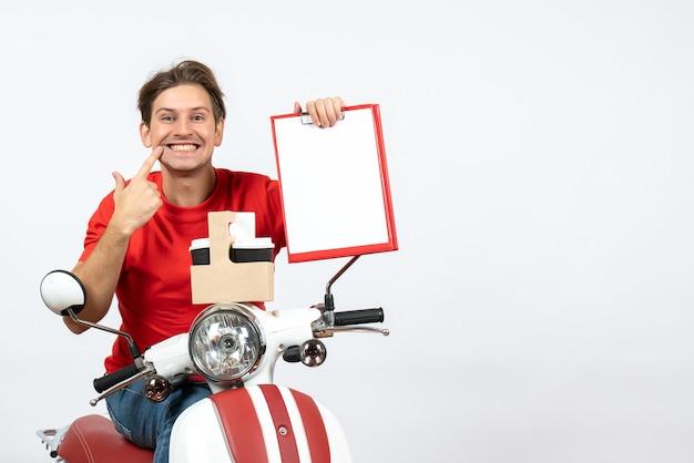 Giovane corriere in uniforme rossa che si siede sul motorino che tiene ordini e documenti che fanno gesto di sorriso sulla parete gialla