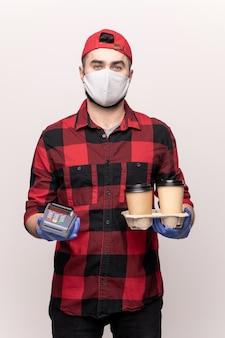 Молодой курьер кафе на вынос в спецодежде, маске и перчатках доставляет два стакана кофе и ждет, пока вы оплатите заказ