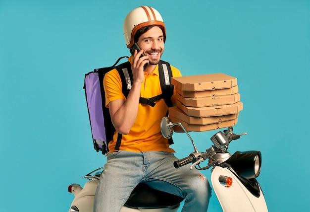 젊은 택배, 열 배낭과 절연 오토바이에 전화 제복을 입은 피자 배달 남자. 빠른 운송 특급 택배. 온라인 주문.