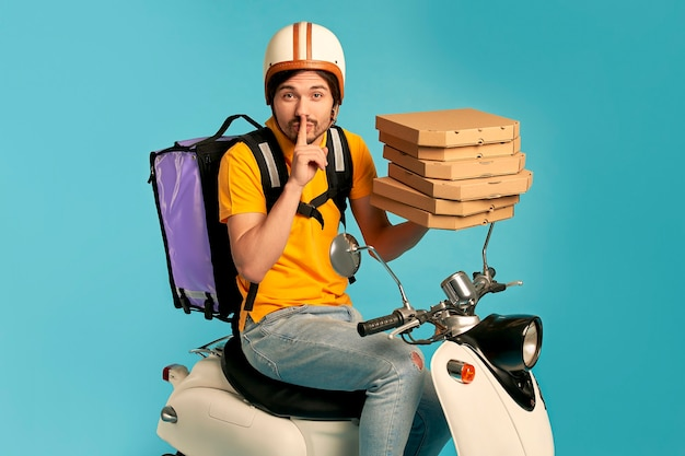 Young courier, pizza delivery man in uniform with thermo backpack on a moped isolated. fast transport express home delivery. online order.
